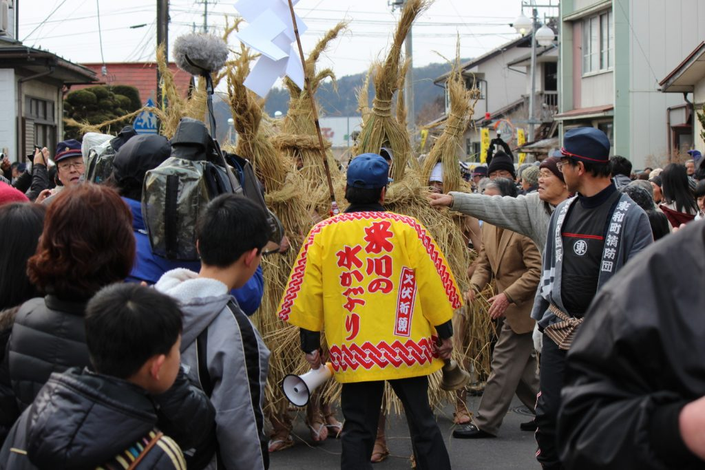 A man wearing a yellow Mizukaburi happi leads the procession of devine messengers, in Yonekawa Mizukaburi , Miyagi, Japan