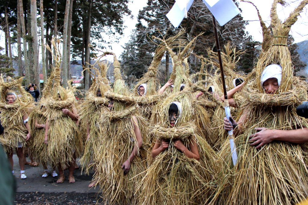 Mizukaburi deities wearing straw costume with soot on the cheeks